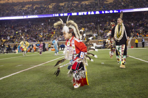 A young Traditional Dancer makes his way across TCF Bank Field as part of  the Native American Heritage Month celebration